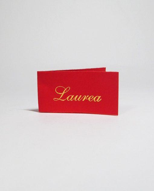 bigliettino rosso con scritta laurea dorata