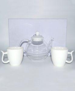 teiera in vetro con tazze in ceramica bianca
