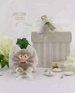 bimbo con libro su altare con sacchetto fiocco e scatola a righe confezione coccole ad emozioni