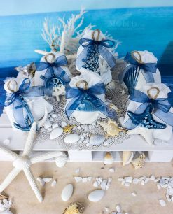 bomboniera pendenti bianchi e blu soggetti marini assortiti su sacchetto bianco con cordoncino linea summer ad emozioni