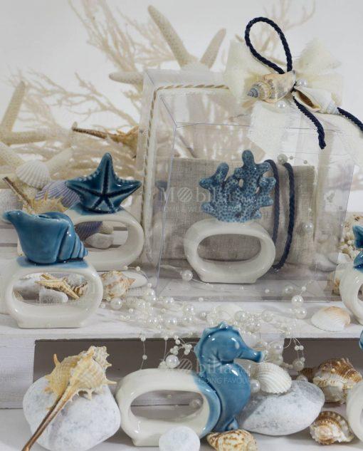 legatovagliolo porcellana bicolore soggetti tema mare assortiti con sacchetto bustina beige con scatola pvc con cordoncino blu e conchiglie con filo di perle collezione nautico ad emozioni