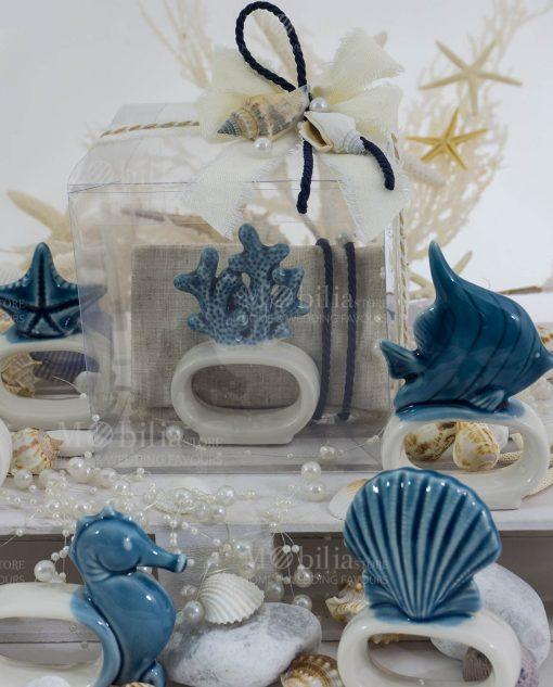 legatovagliolo porcellana bicolore soggetti tema mare con sacchetto bustina beige con scatola pvc con cordoncino blu e conchiglie collezione nautico ad emozioni