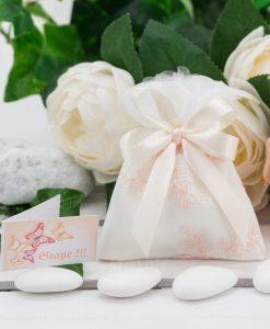 sacchettino bianco con ricami floreali rosa confezionato con doppi fiocchi raso