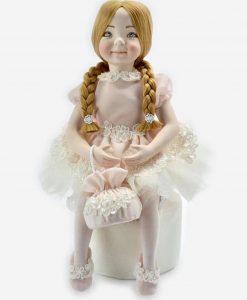 bambolina porcellana capodimonte con trecce con vestito rosa con ricamo con borsetta seduta rdm design