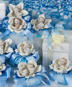 bomboniera sculturina bimbo su fiore modelli assortiti con sacchetto puff azzurro linea baby flower ad emozioni