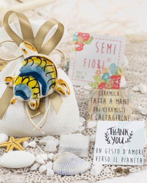 bomboniera solidale tartaruga magnete su sacchetto bianco con nastro oro e cordoncino con semi di fiori legambiente