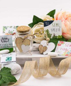 bomboniera solidale legambiente con semi di spezie e di fiori barattolino vetro con pendente doppio cuore bianco e legno