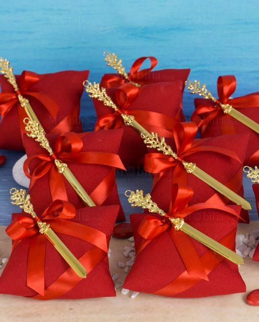bomboniera tagliacarte color oro con corallo linea coral bay emò su cuscino portaconfetti rosso