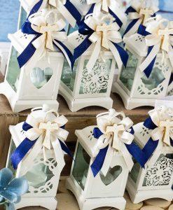bomboniera lanterna bianca decori assortiti applicazione croce tao legno su fiocco blu e panna